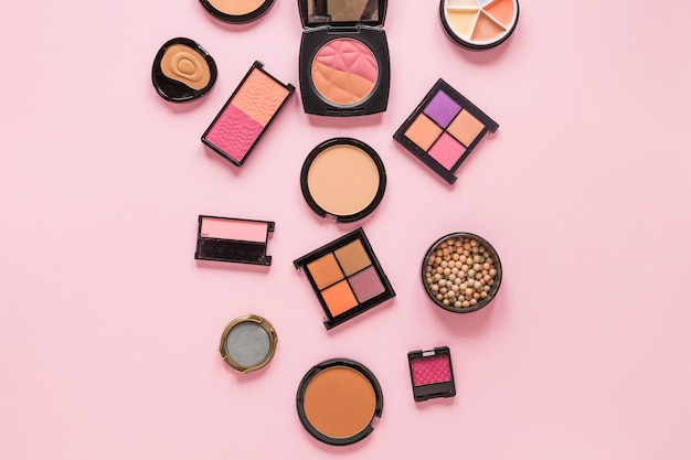 Eye shadows with facial powders on pink table