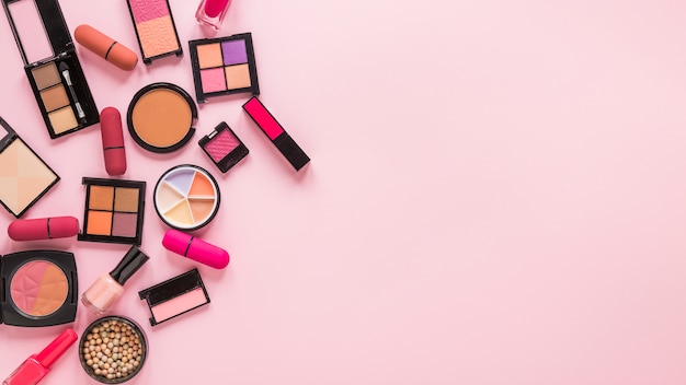 Eye shadows with lipsticks on pink table