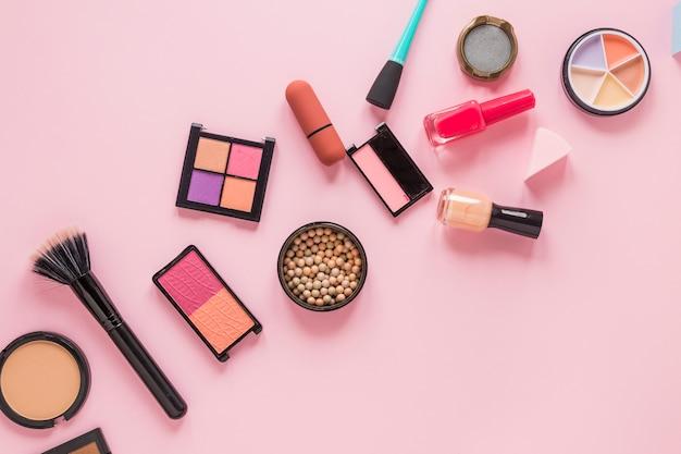 Eye shadows with nail polish on pink table