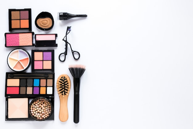Eye shadows with powder brush and comb on table