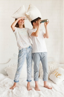 Eye shielding girl standing on bed with her brother looking through telescope
