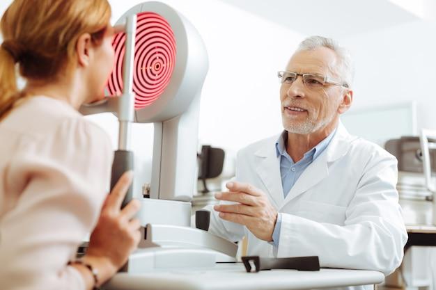 Глаз терапевт улыбается. седовласый глазотерапевт в очках улыбается во время разговора с пациентом