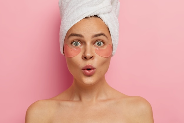 Under eye treatment and body care concept. shocked young caucasian woman applies beauty patches, removes dark circles and puffiness, looks surprisingly at herself in mirror, stands topless indoor
