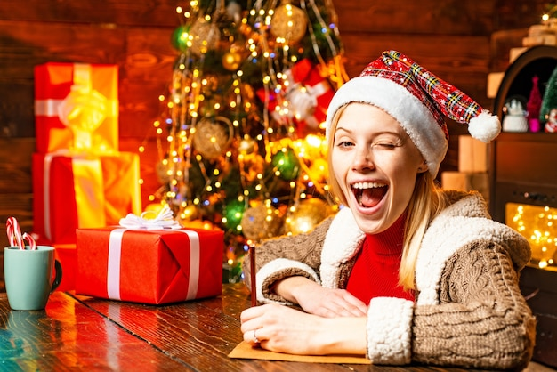 겨울 휴가 배경에서 산타의 모자에 눈 윙크 금발의 아름 다운 여자. 메리 크리스마스와