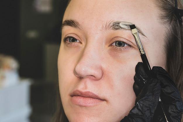 眉毛のカラーリングは美容整形です。眉毛スパトリートメント中にダークブラウンメイクで女性クライアントの眉毛を埋めるエステティシャンのクローズアップ