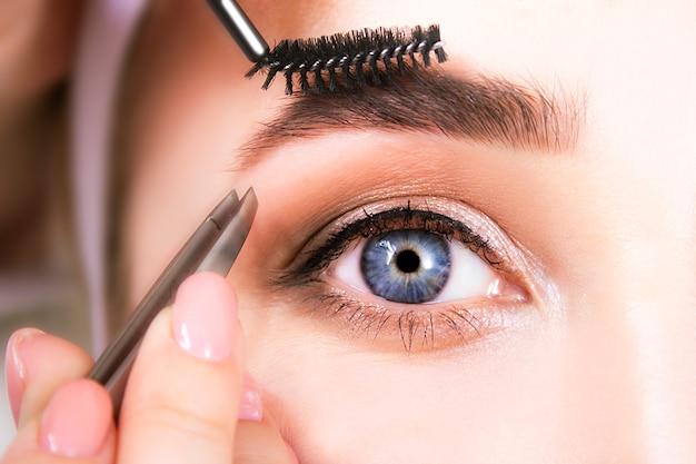 Eyebrow correction and eye makeup close-up.