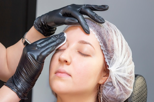 Eyebrow dyeing. beauty saloon. the girl lies with her eyes closed on the eyebrow dyeing procedure. the eyebrow master applies brush to the eyebrows of client.
