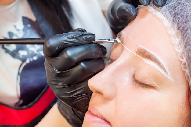 Крашение бровей. салон красоты. девушка лежит с закрытыми глазами на процедуре окрашивания бровей. мастер бровей наносит кисть на брови клиента.