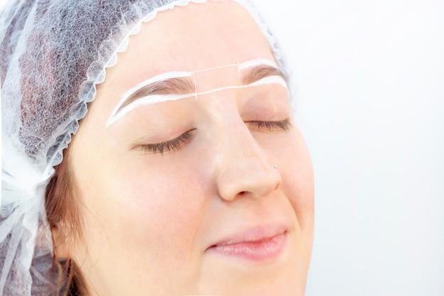 Крашение бровей. салон красоты. девушка лежит с закрытыми глазами на процедуре окрашивания бровей.
