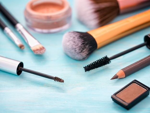 Eyebrow gel or mascara brush and other makeup set on turquoise wooden background.