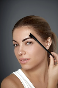 Eyebrow makeup. beautiful woman shaping brows with comb. closeup. beauty girl model with professional makeup contouring eyebrows