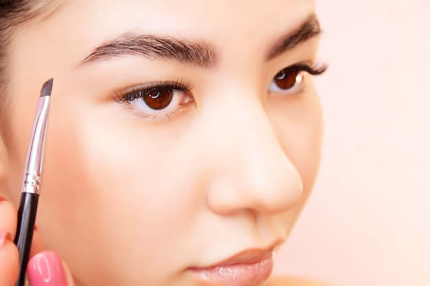 Eyebrow tinting procedure. young brunette woman colors eyebrows in a beauty salon.