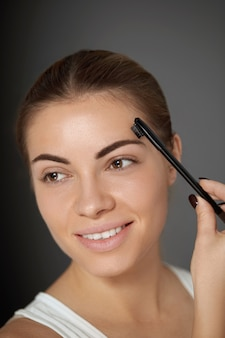 Eyebrows care and  makeup. young woman model shaping brown eyebrows