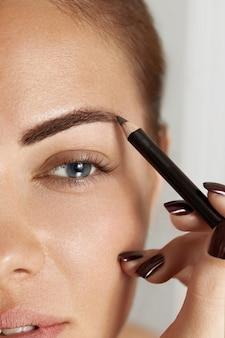 眉毛の矯正。眉ペンシルのクローズアップで眉を形作る美しい若い女性。眉毛とまつげの美容少女モデルをクローズアップ