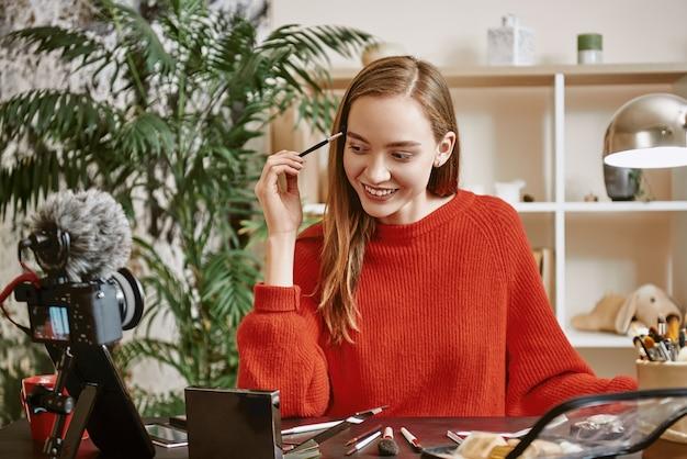 Моделирование бровей улыбается и молодой блоггер в красном свитере, моделируя брови, пока