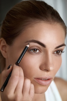 Формирование бровей. молодая женщина красоты с карандашом брови. крупный план красивой девушки с профессиональным макияжем, контурирующим брови карандашом для бровей.