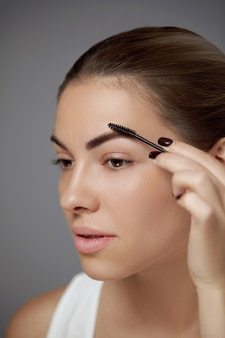 Eyebrows shaping. portrait of beautiful girl with brow pencil. close-up of young woman with professional makeup Premium Photo