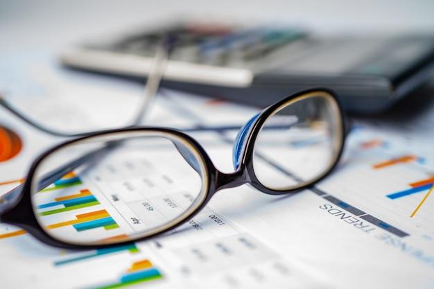 Eyeglass с калькулятором на предпосылке миллиметровки диаграммы.