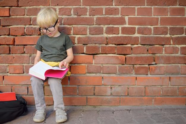 Eyeglass мальчика нося делая домашнюю работу на проломе около школьного здания. обратно в школу концепции.