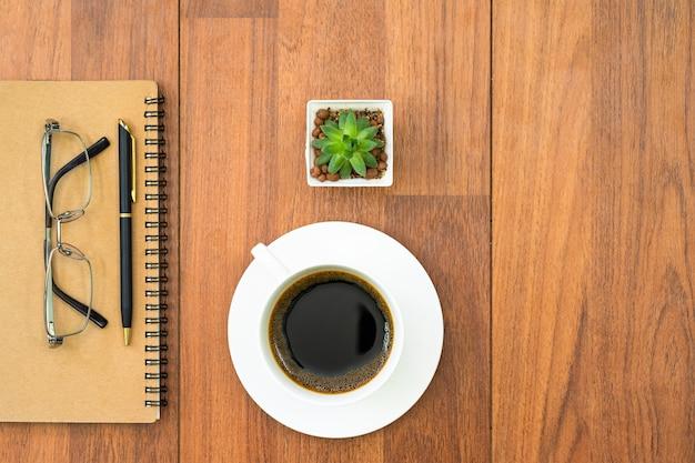 Eyeglasse와 나무 갑판에 커피 컵과 메모장