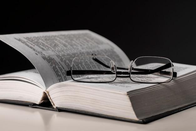 Очки и открытая книга на столе. концепция образования и мудрости.