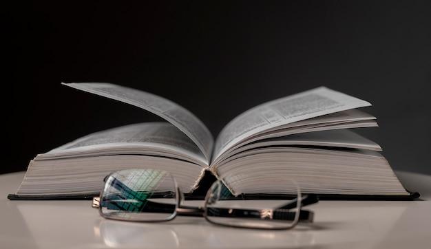 Очки и открытая книга на столе. концепция образования.
