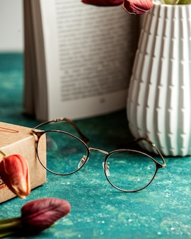 Eyeglasses book vase and tulips on table