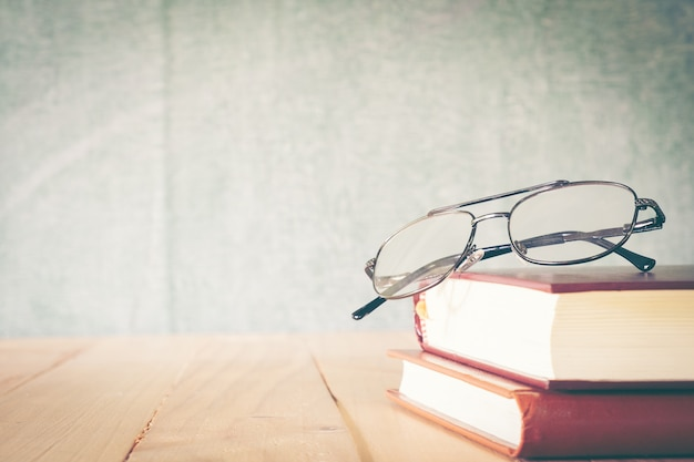 Eyeglasses and books on chalkboard background