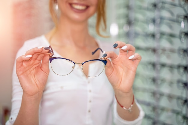 안경 근접 촬영입니다. 여자의 손에 안경입니다. 안경을 제시합니다. 확대합니다. 배경을 흐리게 합니다.