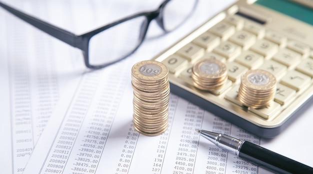 Очки, монеты, калькулятор, ручка на финансовых документах. бизнес. финансы