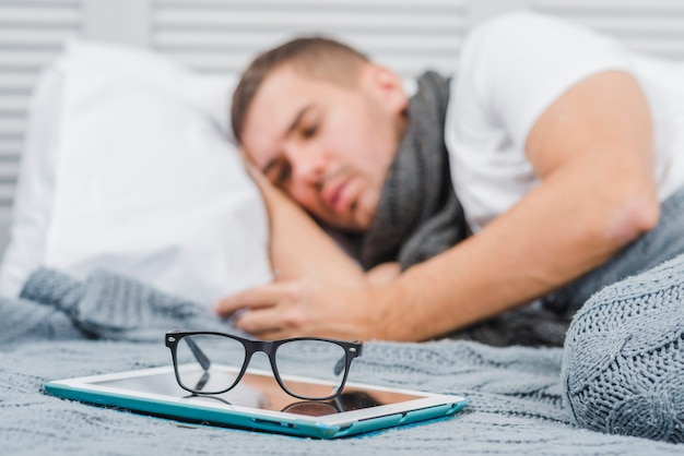 Eyeglasses on digital tablet in front of a sick man lying over bed