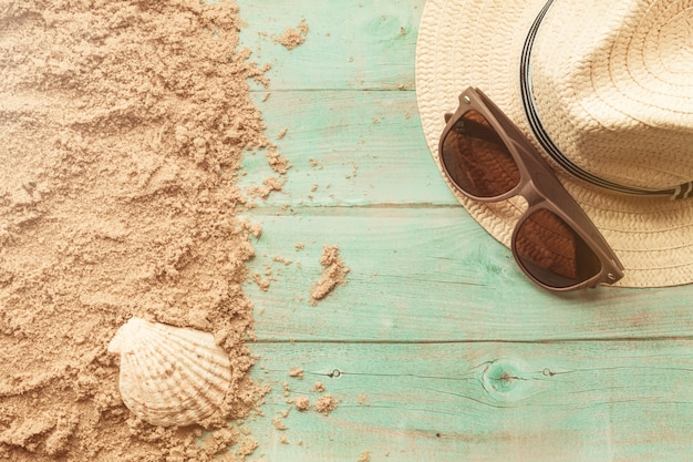 Eyeglasses and hat on wood with sand
