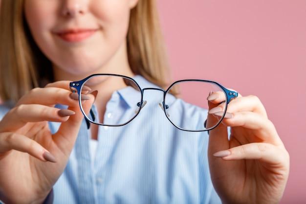 손에 안경. 여성의 손에 비전을위한 파란색 유행 금속 안경. 눈 건강 검사, 분홍색 벽 위에 안경을 통한 시력 교정.