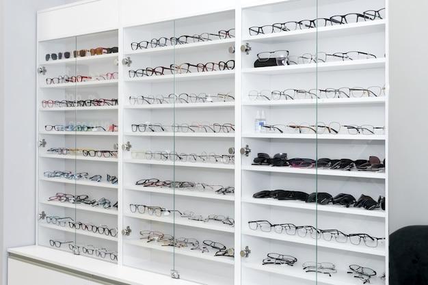 光学店の眼鏡、ファッション、ショッピングモールの白い棚にあるさまざまな眼鏡。眼鏡技師の眼鏡の列、選択的な焦点