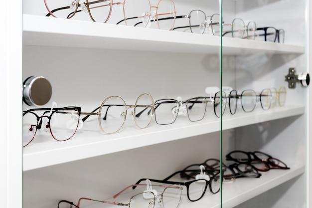 Очки в оптическом магазине, моде, разные очки на белой полке в торговом центре. ряд очков в оптике, выборочный фокус