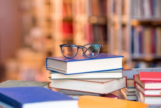도서관에서 책 위에 누워 있는 안경. 복사 공간이 있는 이미지