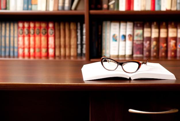 열린 책 및 배경에 다른 많은 책에 누워 안경