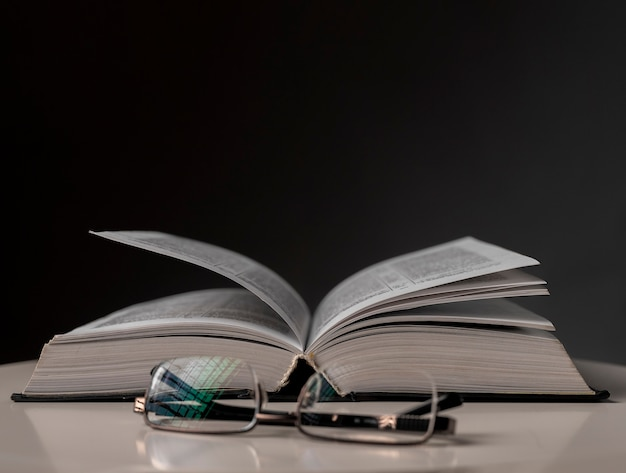 Eyeglasses and open book on black background with copy space