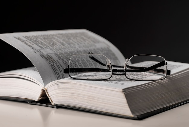 Eyeglasses and open book on table. education and wisdom concept.