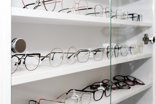 Eyeglasses in optical store, fashion, different glasses on white shelf in shopping mall. row of glasses at an opticians, selective focus