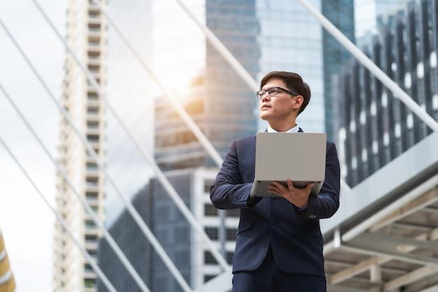 Портрет eyeglasses азиатского бизнесмена нося используя компьтер-книжку пока стоящ outdoors около здания
