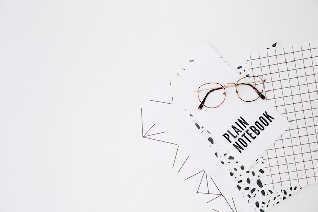 Eyeglasses on plain notebook and pages on white background