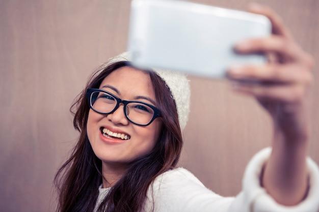 Усмехаясь eyeglasses азиатской женщины нося принимая selfie