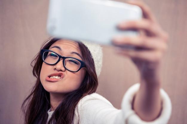 Eyeglasses азиатской женщины нося делая стороны и принимая selfie