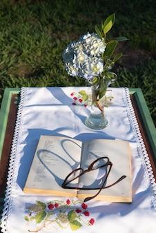 眼鏡は庭の日没時に開いた本の上に影を落とす