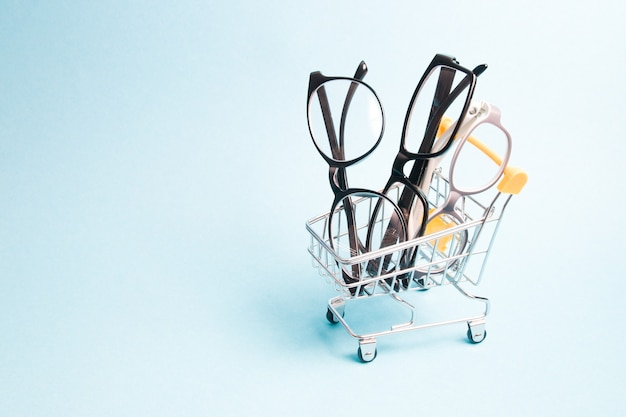 Eyeglasses in a small shopping trolley on blue surface