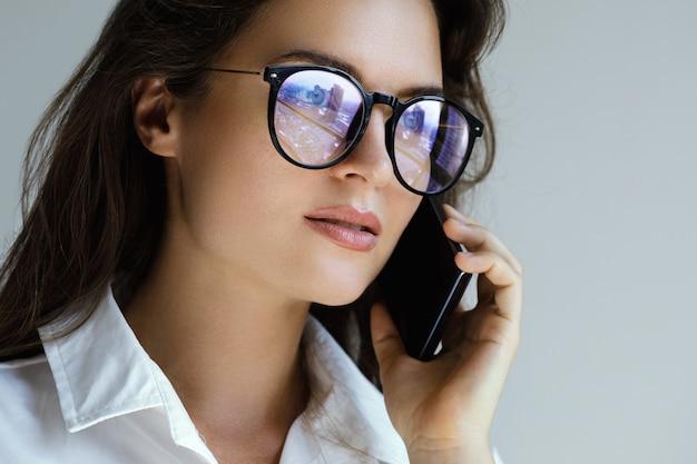 Молодая коммерсантка в eyeglasses говоря smartphone