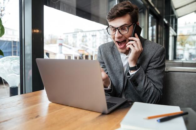 Счастливый удивленный бизнесмен в eyeglasses сидя таблицей в кафе пока говорящ smartphone и использующ портативный компьютер