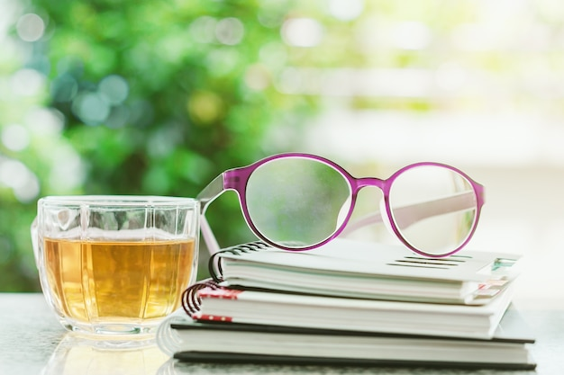 Eyeglasses on spiral notebooks with cup of tea against blurred natural green background