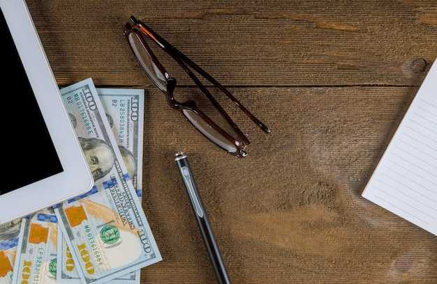 Eyeglasses on tablet pc with dollar bills and pen on wooden table at close up
